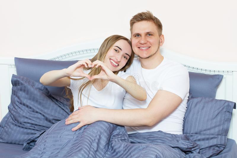 Young Beautiful Couple Lying On Bed Forming Heart Shape With Hand. Beautiful young woman lies with her husband in the bedroom and stock photography