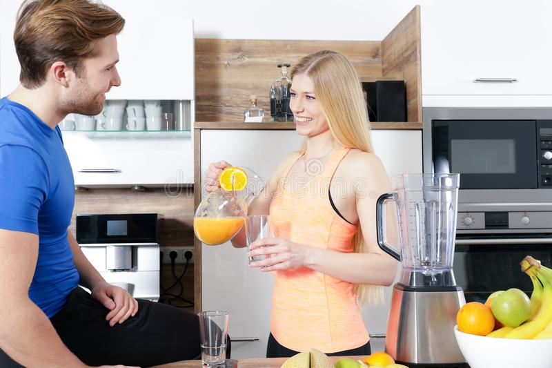 Young beautiful couple is making a smoothy with a mixer stock photos