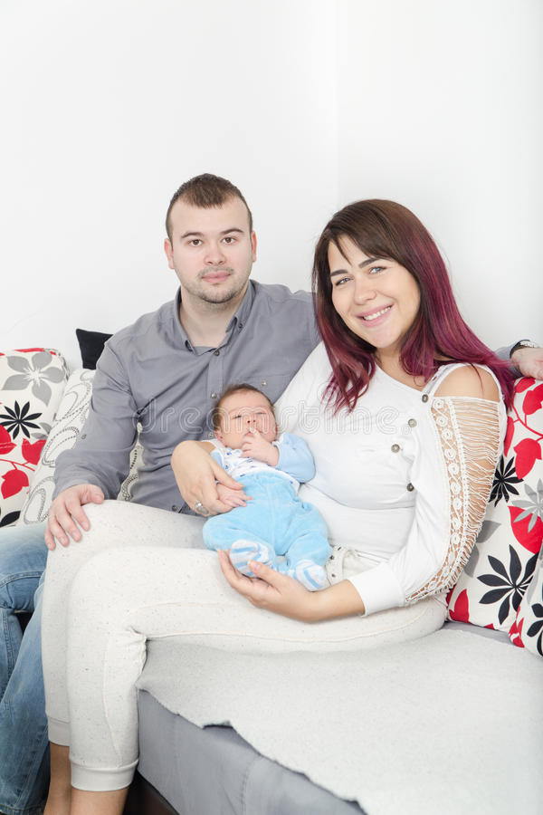 Young Beautiful Couple with New Baby at Home. Portrait of a Smiling Happy Family with the Kid in Bright Domestic Background. Man and Woman with Newborn Child royalty free stock photo
