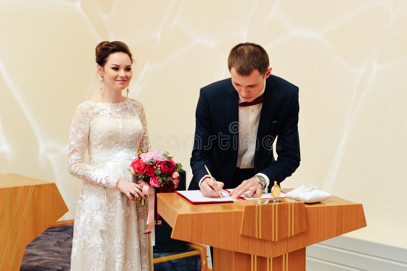 Young beautiful couple puts a ring on the hand, the newlyweds exchange rings stock photo