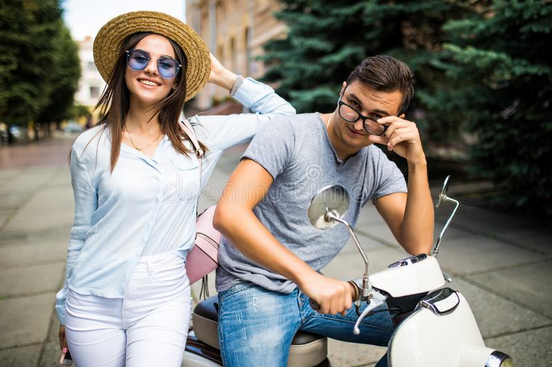 Young beautiful couple riding on motorbike city street summer europe vacation. royalty free stock images