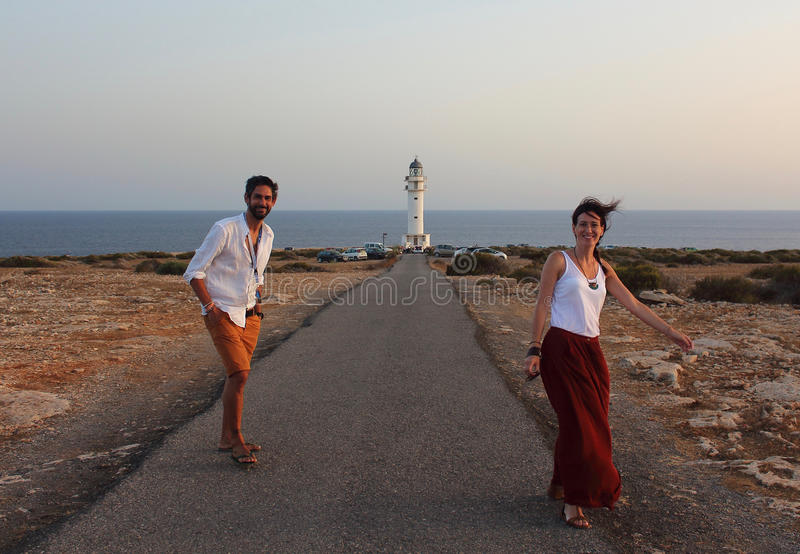 Young beautiful couple`s portrait with Cap de Barberia`s lighthouse on soft background, Formentera, Balearic Islands, Spain.  stock photo