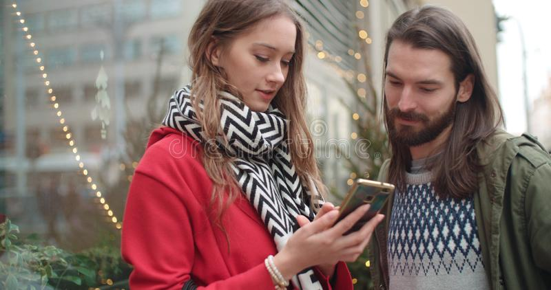 Young beautiful couple share memories and pictures on social media with online mobile app. royalty free stock photos