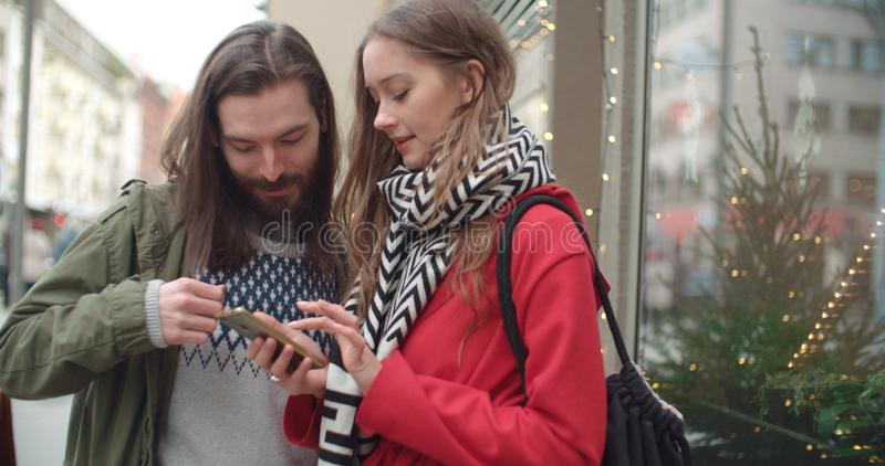 Young beautiful couple share memories and pictures on social media with online mobile app. stock photo