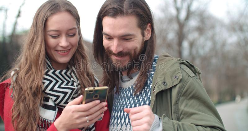 Young beautiful couple share memories and pictures on social media with online mobile app. royalty free stock images
