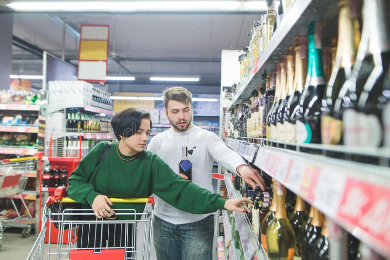 A young beautiful couple with a shopping cart chooses wine from supermarket shelves. The young family is buying wine stock photos