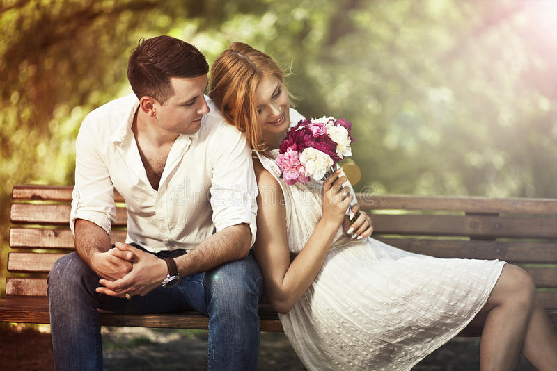 Young beautiful couple sitting in the park and man proposing wo royalty free stock images