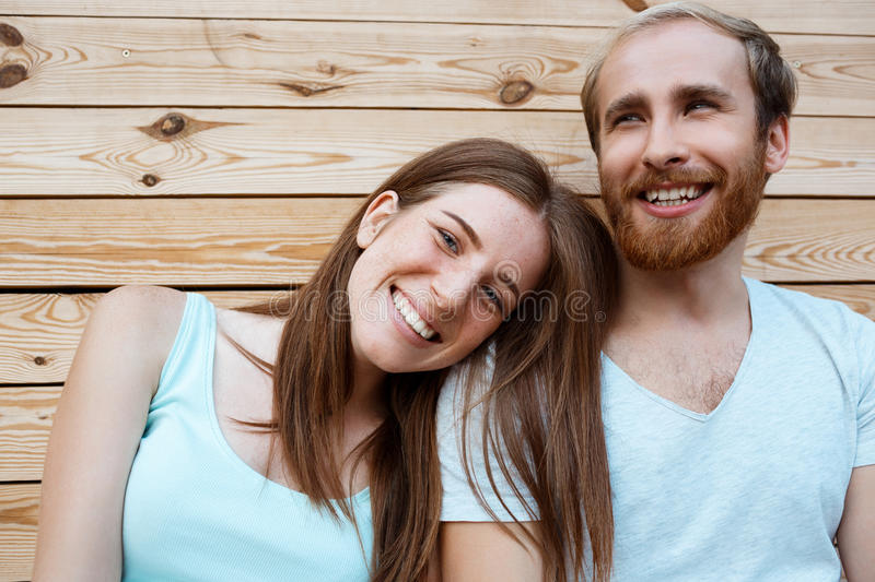 Young beautiful couple smiling, posing over wooden boards background. royalty free stock photography