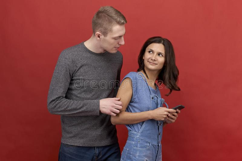 Young beautiful couple standing on a red background. Brunette girl texting on the phone stock image