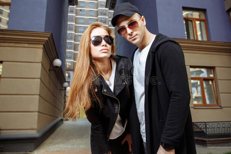 Young beautiful couple in stylish fashion clothes with sunglasses on the street stock images