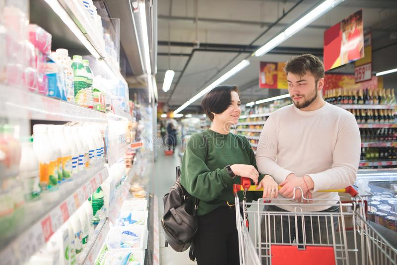 Young beautiful couple at a supermarket near the counter. Couple with a cart carries shopping in a supermarket royalty free stock photo