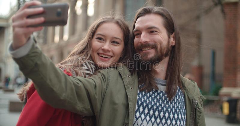 Young beautiful couple taking selfie in a city. royalty free stock images