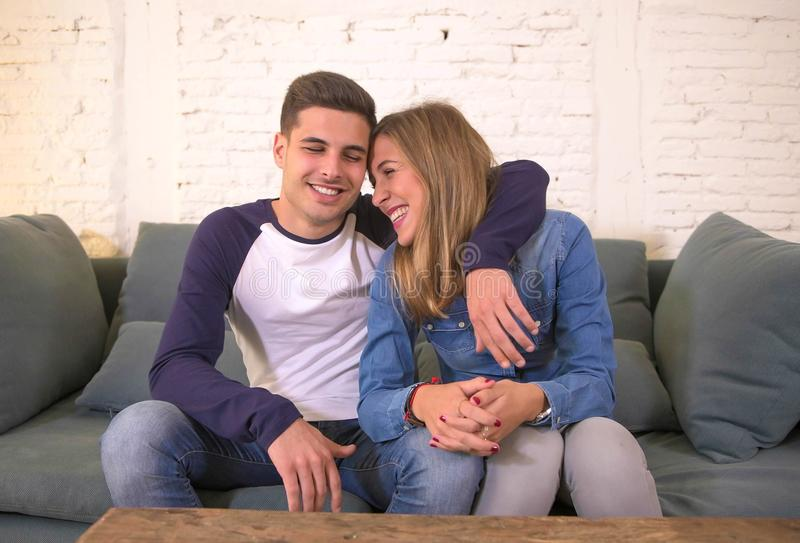 Young beautiful couple teenagers or 20s romantic girlfriend and boyfriend in love smiling happy cuddling on home sofa couch in rom. Ance dating and sweet royalty free stock photos