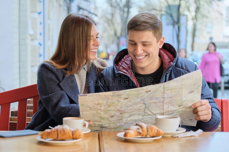 Young beautiful couple of tourists resting in outdoor cafe, reading city map, drinking coffee with croissants royalty free stock image
