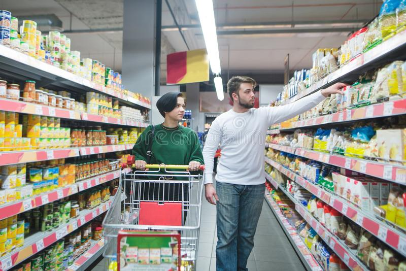 A young beautiful couple walking with a supermarket cart and choosing products. Family shopping at a supermarket royalty free stock photos