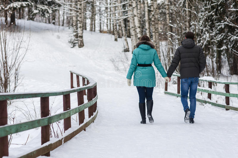 Young beautiful couple walking in winter forest. Couple playing with snow in winter in a park royalty free stock image