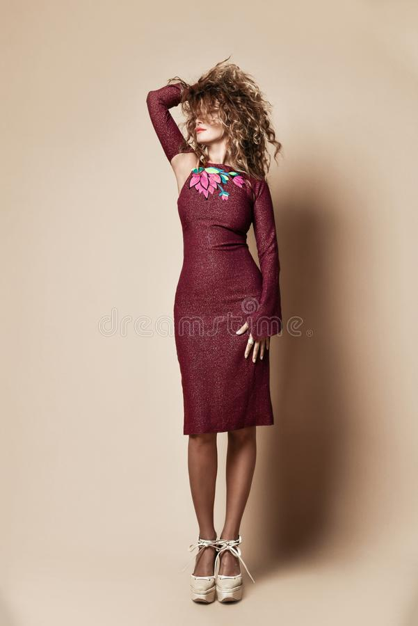 Young beautiful curly hair woman posing in new dark purple fashion winter dress on beige. Background stock image
