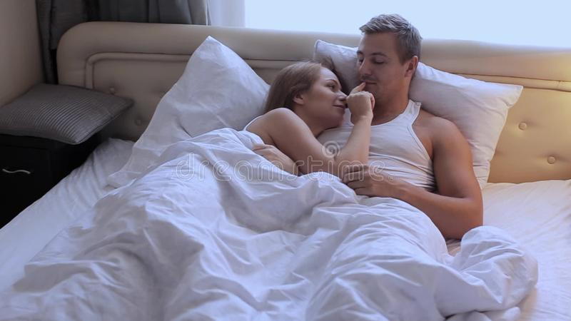 . Young beautiful cute couple lying in bed in the morning  embracing and  smiling  Lifestyle  embrace