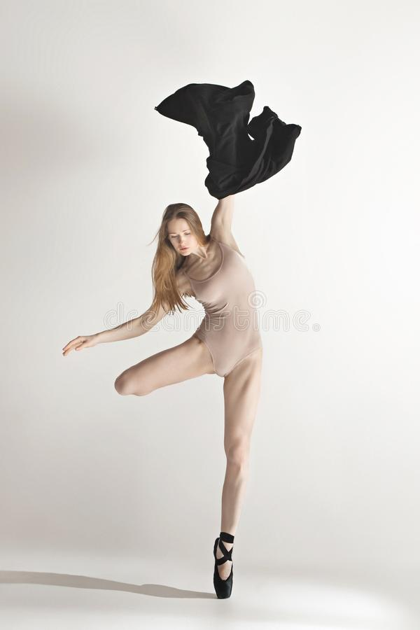 Young beautiful dancer in beige swimsuit dancing on gray background royalty free stock image