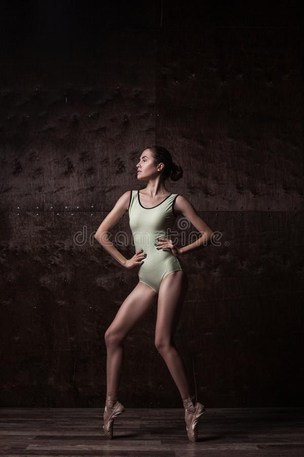 Young beautiful dancer in beige swimsuit. Posing on light grey studio background royalty free stock image