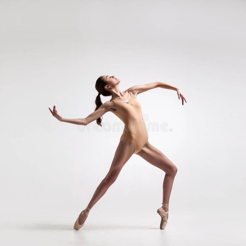 Young beautiful dancer in beige swimsuit. Posing on toes on white studio background royalty free stock photo