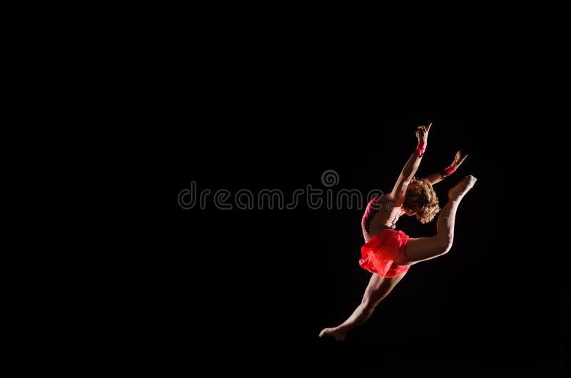 Young beautiful dancer gymnastics jumping in studio stock image