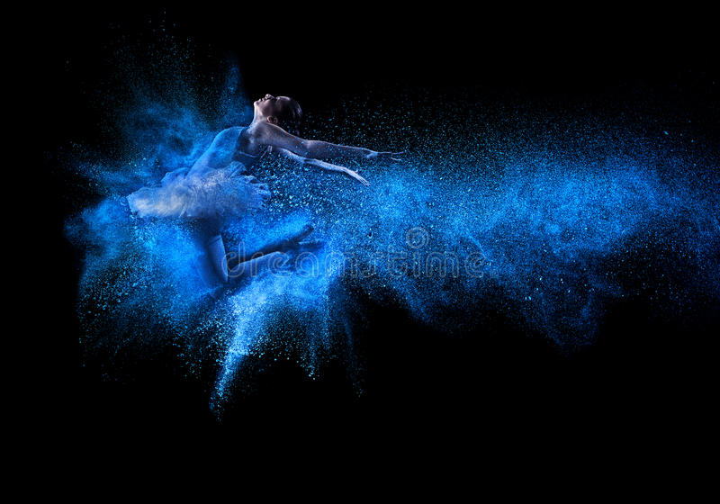 Young beautiful dancer jumping into blue powder cloud stock images