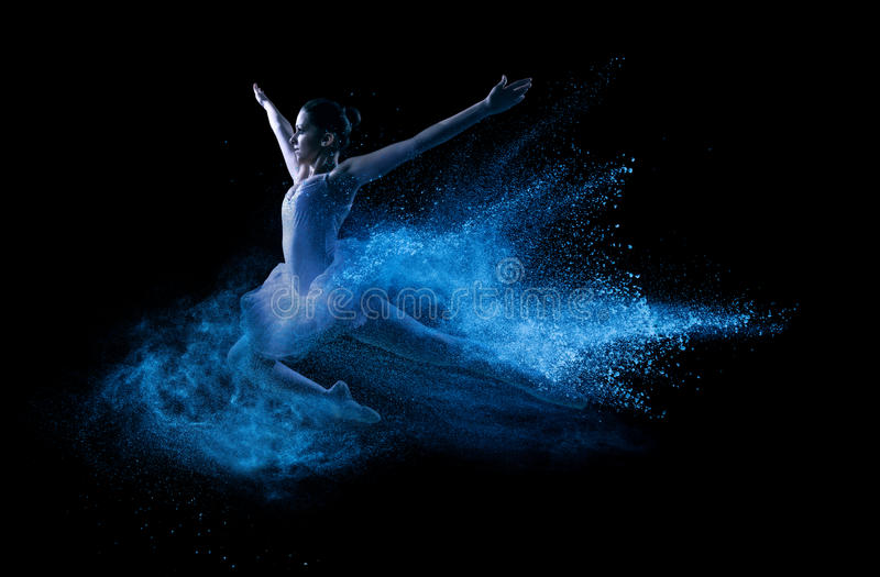Young beautiful dancer jumping into blue powder cloud.  stock photo