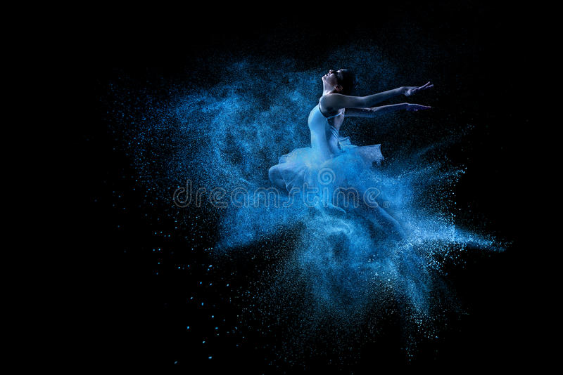Young beautiful dancer jumping into blue powder cloud.  royalty free stock images