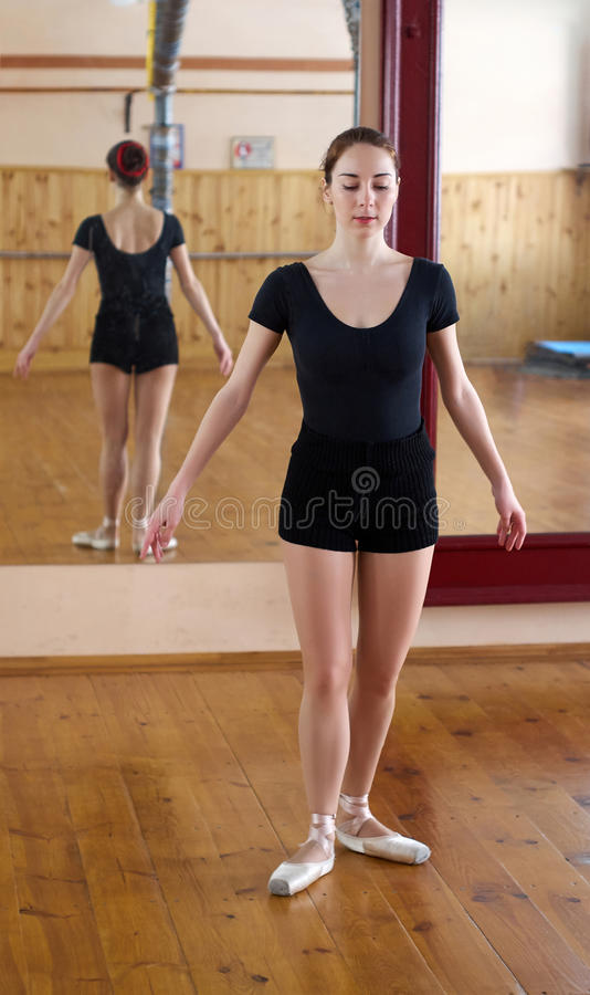 Young beautiful dancer posing in fitness center on a studio mirror background stock photography