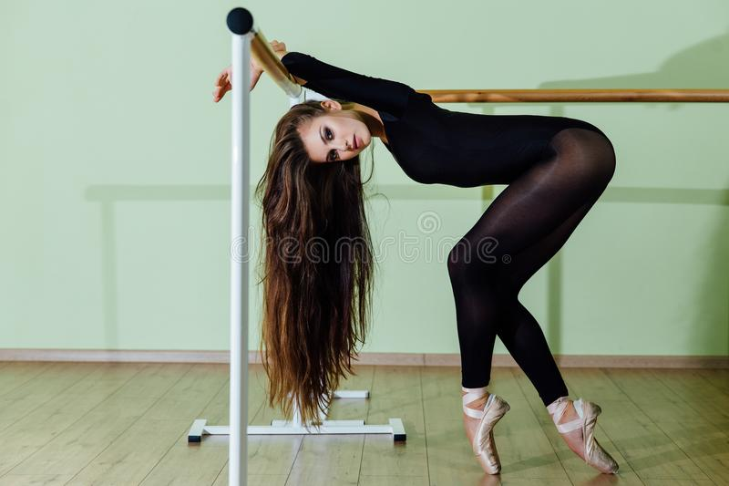 Young beautiful dancer posing in studio wit Ballet bar on tiptoe. Modern brunette. Young beautiful dancer posing in studio wit Ballet bar on tiptoe. Modern royalty free stock photos