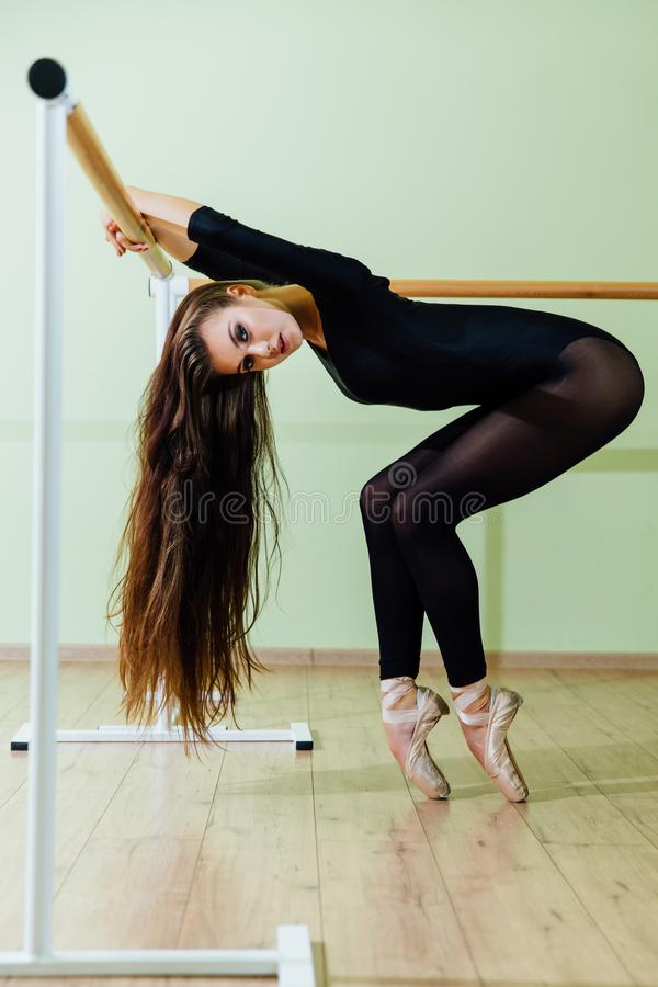 Young beautiful dancer posing in studio wit Ballet bar on tiptoe. Modern brunette. royalty free stock photography