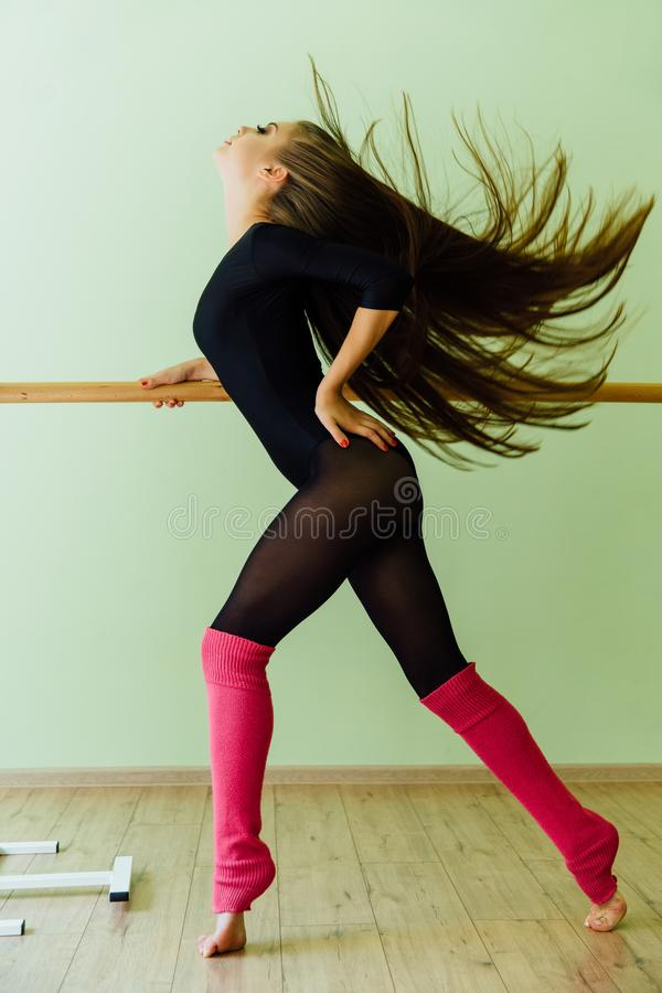 Young beautiful dancer posing in studio wit Ballet bar on tiptoe. Modern brunette. stock photography