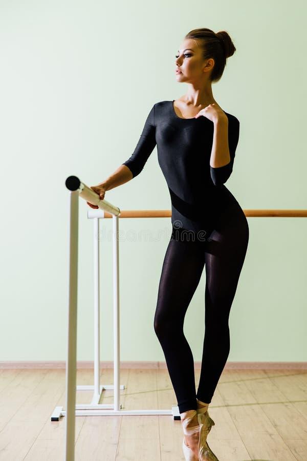 Young beautiful dancer posing in studio wit Ballet bar on tiptoe. Modern brunette. stock image