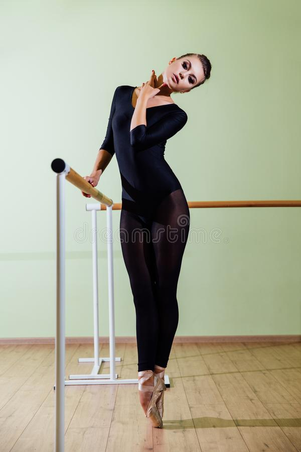 Young beautiful dancer posing in studio wit Ballet bar on tiptoe. Modern brunette. Young beautiful dancer posing in studio wit Ballet bar on tiptoe. Modern royalty free stock photo