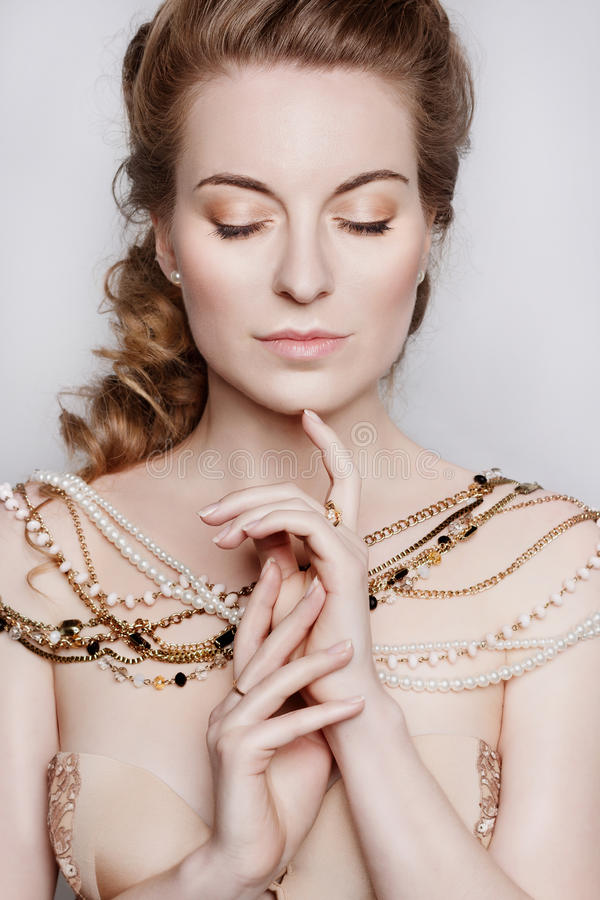 Young beautiful dark blonde woman in a gold necklace. Portrait of a young beautiful dark blonde woman in a gold necklace. She wears satin beige dress. She has stock photos