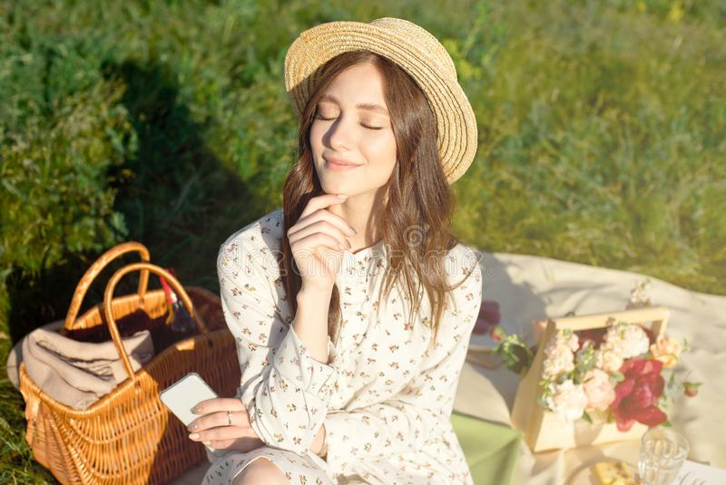 Young beautiful, dark-haired girl in a straw hat at sunset picnic in the field. Autumn. Camping fruits and drinks in a royalty free stock photos