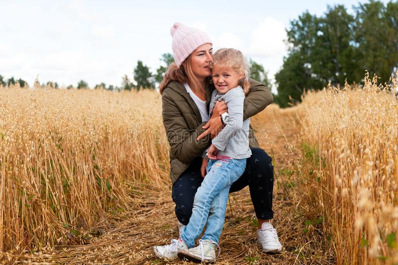Young beautiful darkhaired woman with baby. Outdoor atmospheric lifestyle photo of young beautiful darkhaired women mother with baby in knitting hat in sunny stock photo