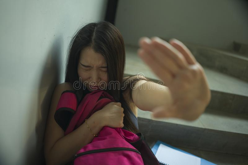 Young beautiful depressed Asian Japanese college student sitting on staircase victim of abuse feeling scared and lonely being stock photography