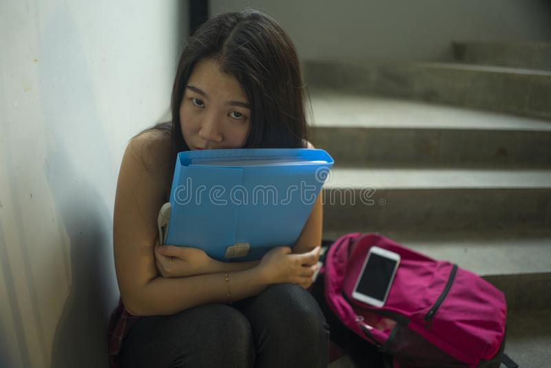 Young beautiful depressed Asian Korean college student sitting on campus staircase victim of abuse feeling scared and lonely being royalty free stock photography