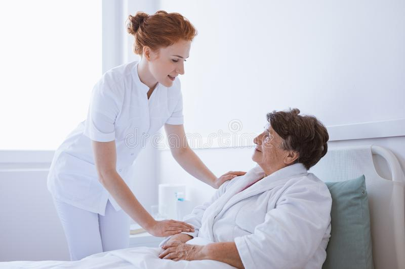 Young beautiful doctor and senior patient at hospital royalty free stock image