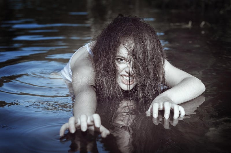 Young beautiful drowned ghost woman in the water. Outdoor royalty free stock image