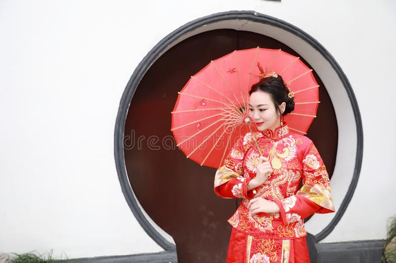 Young, beautiful and elegant Chinese woman wearing a typical Chinese bride`s silk red dress, adorned with golden phoenix and drago royalty free stock photography