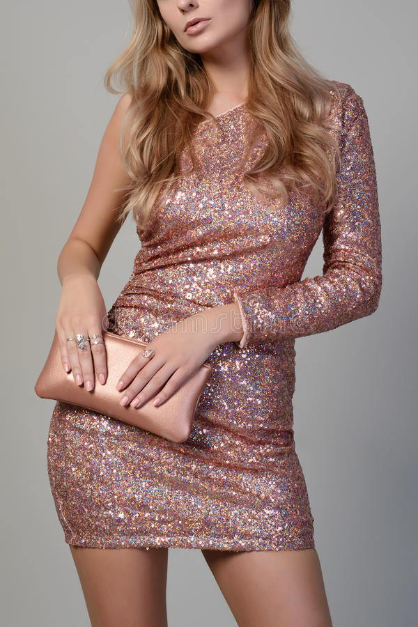 Young beautiful elegant woman in fashionable paillettes dress with small bag royalty free stock photos