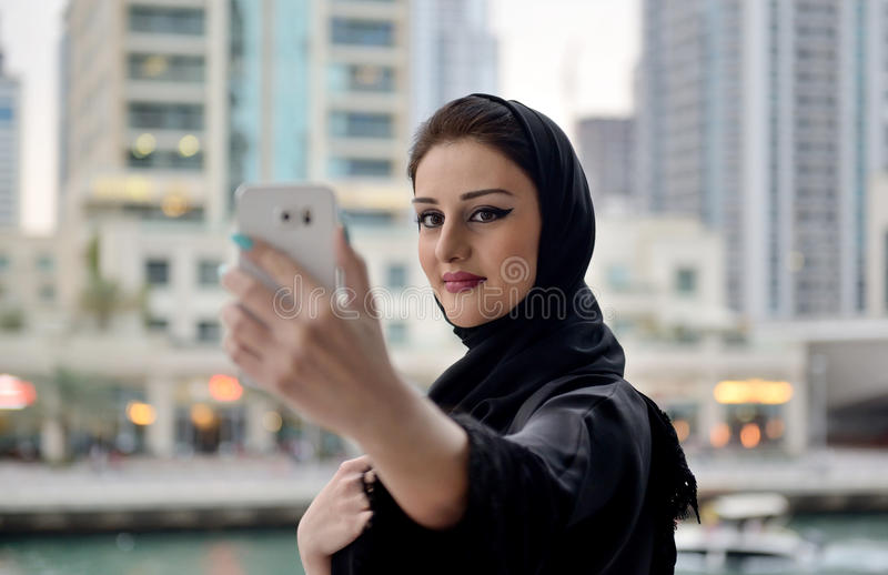 Young and beautiful Emirati woman taking selfie stock photography