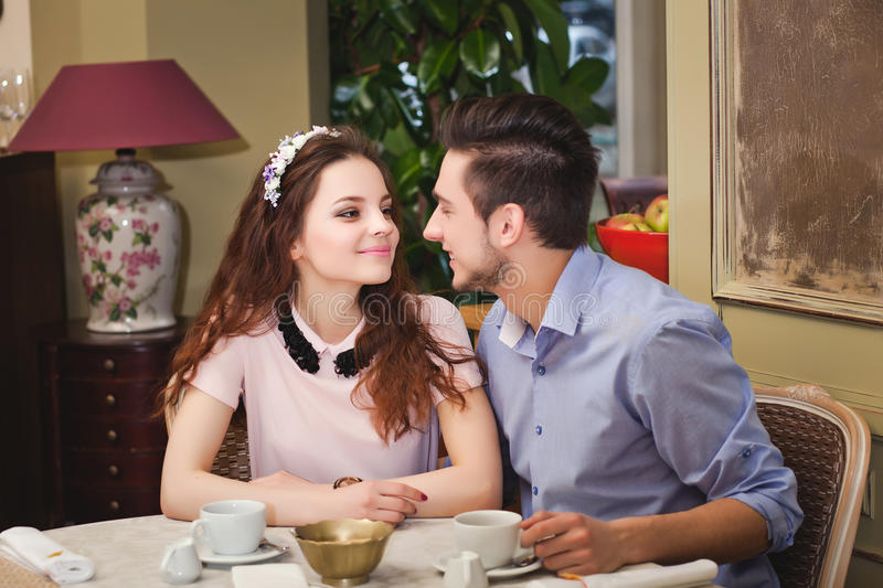 Young beautiful enamored couple sitting at a table in a cafe stock photos