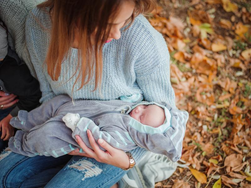 A girl holding a sleeping baby and watching her. stock photography