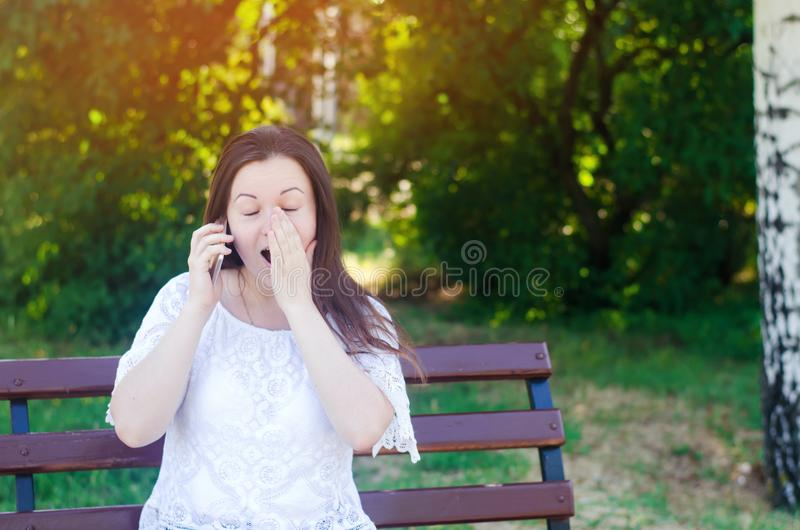 Young beautiful European girl brunette speaks on the phone in a city park and covers her face with her hands. surprised woman. une stock image