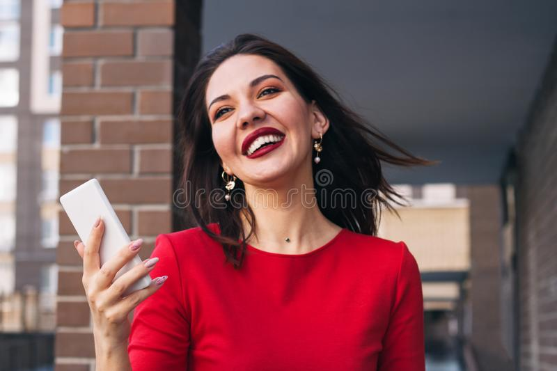 beautiful excited happy woman with red lipstick and wearing red dress holding mobile phone outside, selective focus royalty free stock images