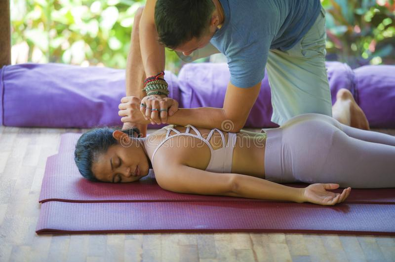 Young beautiful and exotic Asian Balinese woman lying on studio mat receiving traditional Thai massage by masseur at tropical stock photo